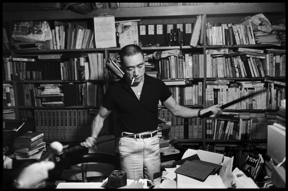 Yukio Mishima with books and sword